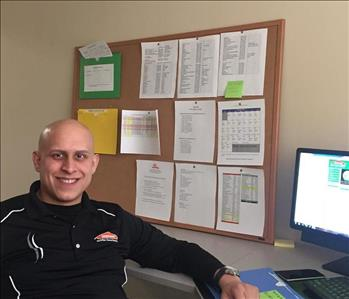 Male wearing a black SERVPRO shirt, in front of a computer
